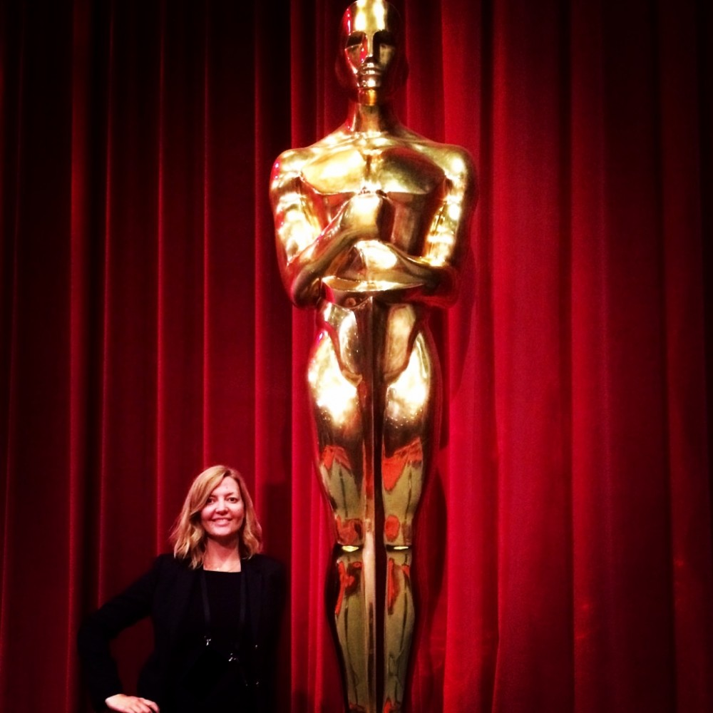Vanessa J. Noon in front of an Oscars statue.