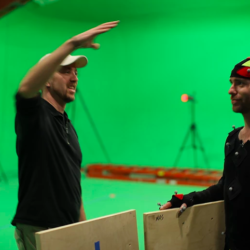 Man in front of green screen with actor in mo cap suit