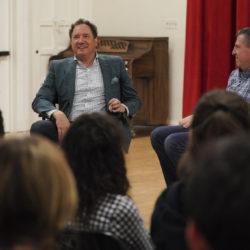 Men speaking at front of classroom