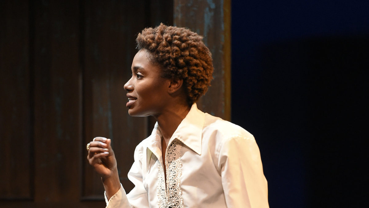 woman onstage delivering lines in white blouse