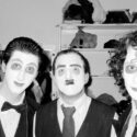 Three men wearing suits and stage makeup behind the scenes of a production