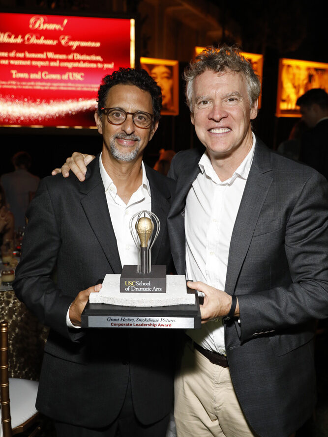 Honoree Grant Heslov and Tate Donovan hold Heslov's the award statue for Corporate Leadership Award